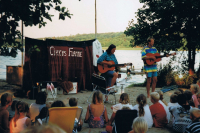 Circus Flame (Wizard of the island Samsø). Children are sitting at the beach and listening to live music