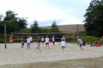Children and youth are playing beach volleyball