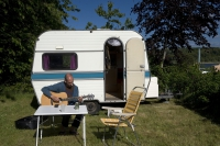 Camper plays the guitarin front of his caravan (Photo: Lars Horn)