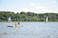 Windsurfers and bathing campers at the lake