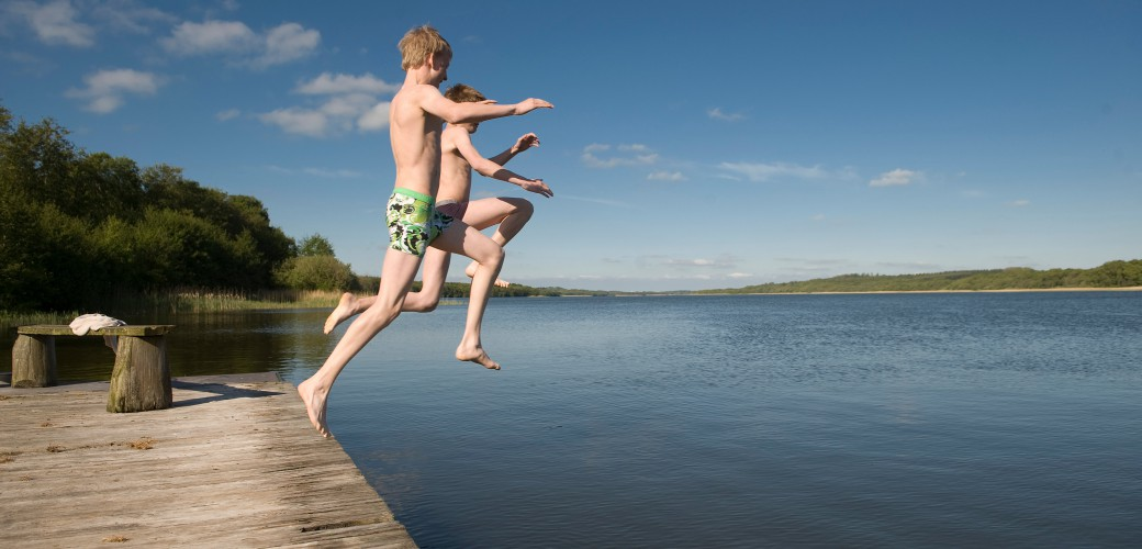 Jump in to the lake from the wooden pier (the big raft) and swim out to the small raft